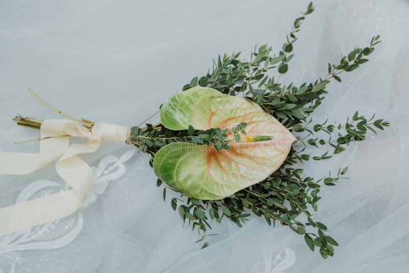 Букет ` s невесты Красивый Bridal букет цветков и растительности, украшенный с длинной лентой шелка лежит на белизне стоковые изображения