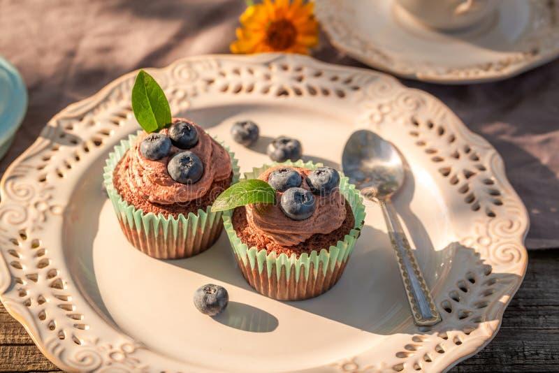 Булочка шоколада со свежими голубиками и сливк на плите стоковая фотография