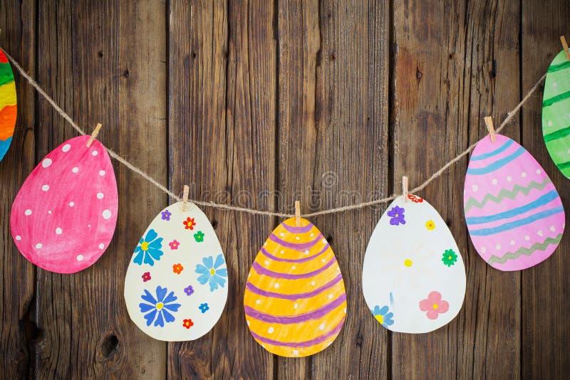 Бумажная пасха покрасила яйца покрасила вид на зажимках для белья на backgr стоковое изображение
