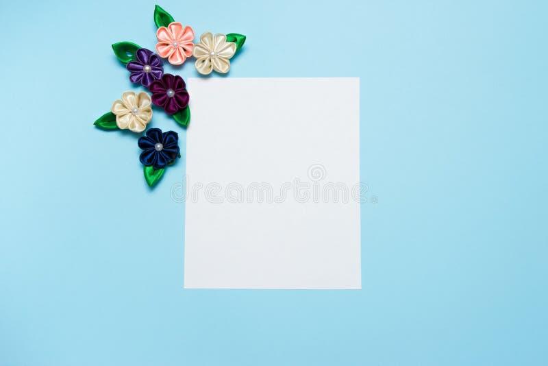 Бумажный пробел с цветками сатинировки и космос экземпляра на голубой предпосылке Взгляд сверху, плоское положение против детеныш стоковая фотография