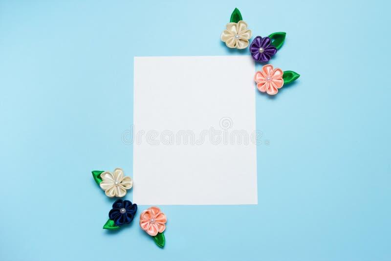 Бумажный пробел с цветками сатинировки и космос экземпляра на голубой предпосылке Взгляд сверху, плоское положение против детеныш стоковое изображение