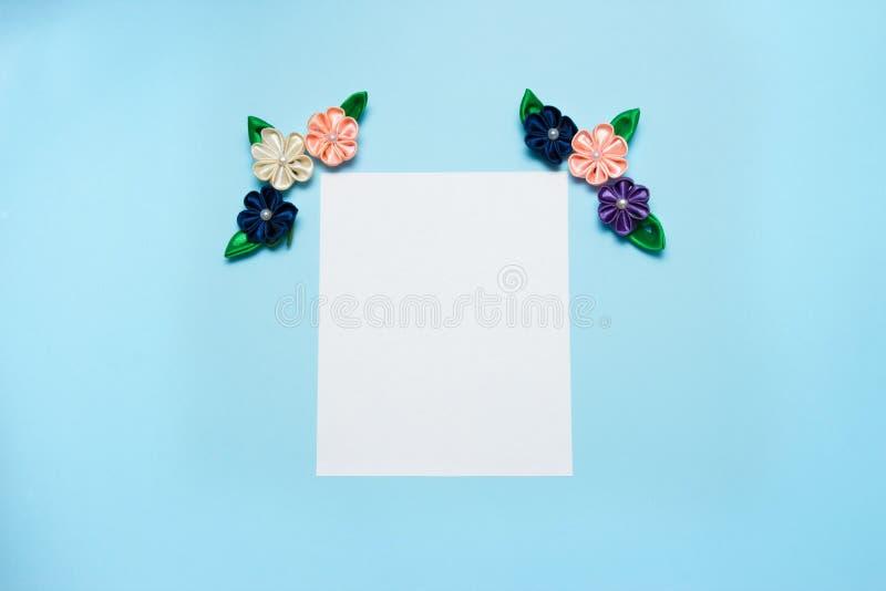 Бумажный пробел с цветками сатинировки и космос экземпляра на голубой предпосылке Взгляд сверху, плоское положение против детеныш стоковое фото