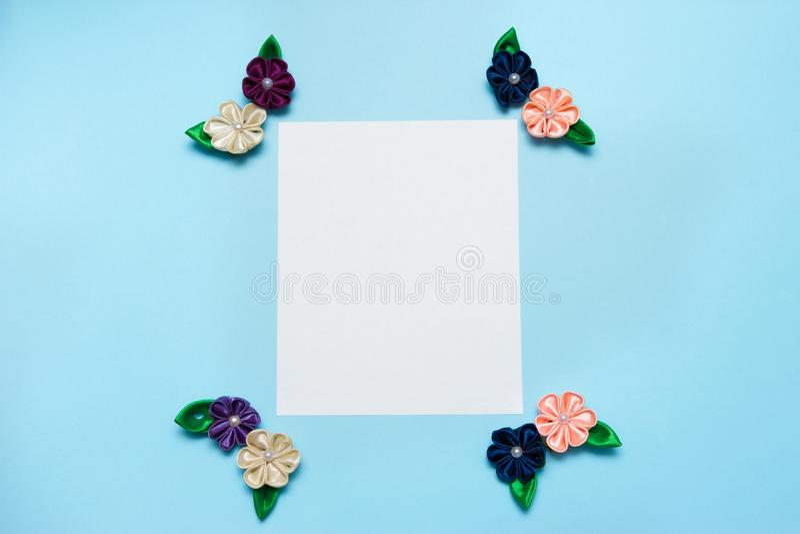 Бумажный пробел с цветками сатинировки и космос экземпляра на голубой предпосылке Взгляд сверху, плоское положение против детеныш стоковые изображения