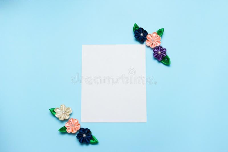 Бумажный пробел с цветками сатинировки и космос экземпляра на голубой предпосылке Взгляд сверху, плоское положение против детеныш стоковое фото rf