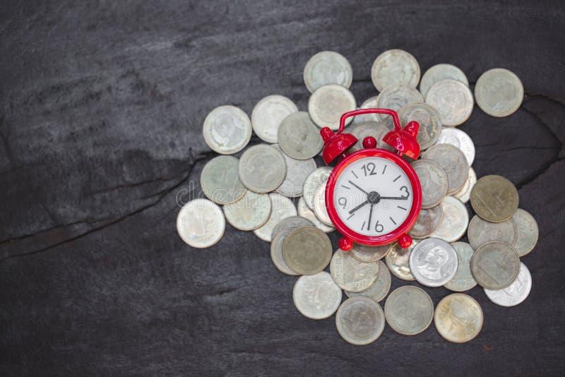 Будильник и монетки на деревянном столе, сбережения денег, вклад, растя концепция, штабелируя растя монетки, сохраняют деньги для стоковые изображения rf
