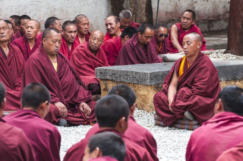 Буддийские монахи сидя на том основании и chanting, сыворотки монастырь, Тибет стоковое изображение rf
