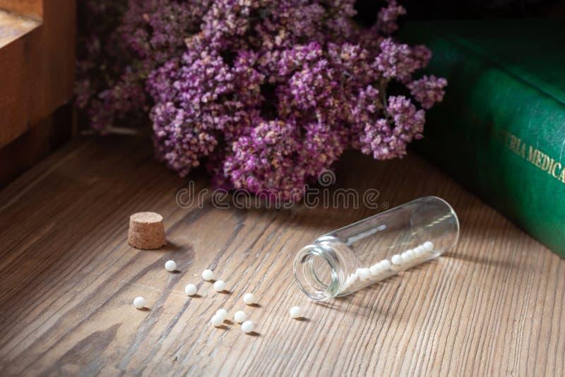 Бутылка гомеопатических глобул с высушенными травами и medica materia стоковое фото