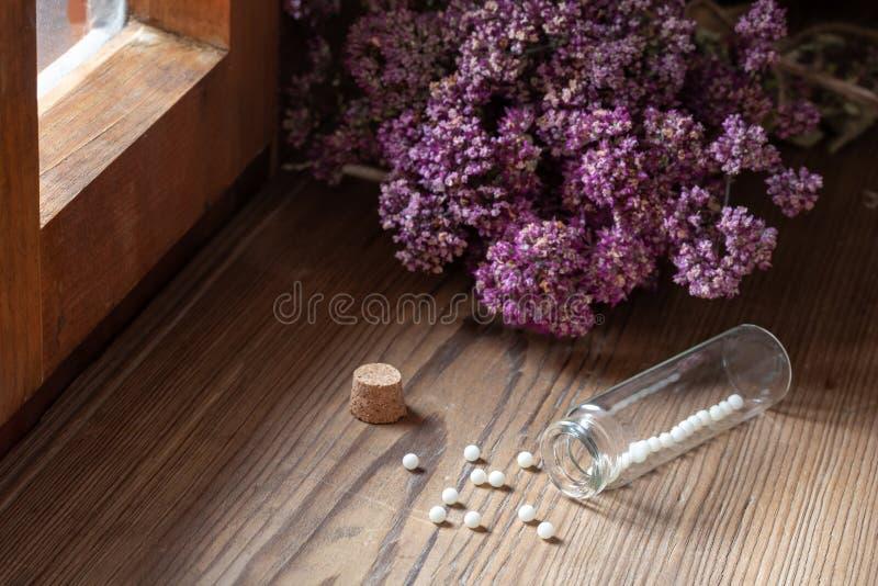 Бутылка гомеопатических таблеток с высушенными травами стоковое фото rf