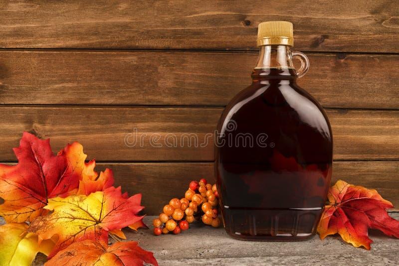 Бутылка сиропа клена на деревянной предпосылке планки стоковая фотография