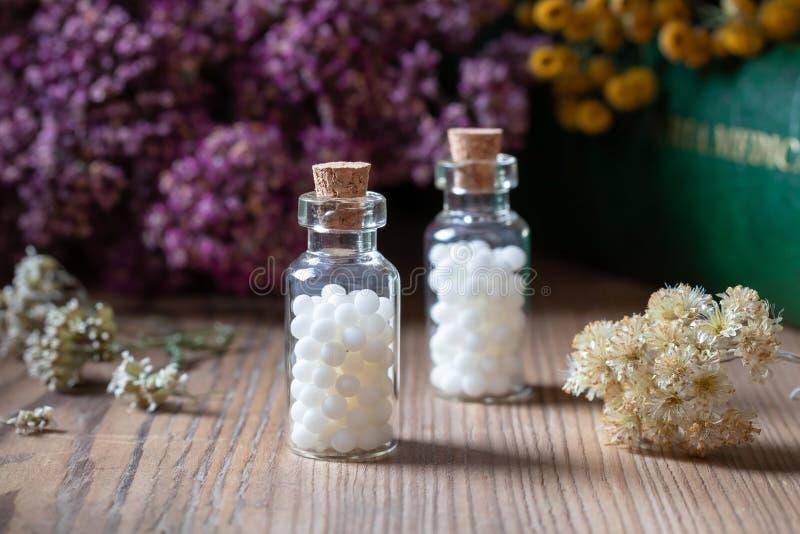 Бутылки гомеопатических таблеток с высушенными травами стоковая фотография