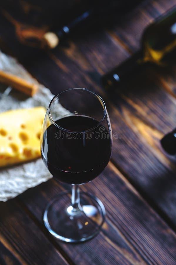 2 бутылки с бокалами и частью сыра на деревянной предпосылке стоковая фотография