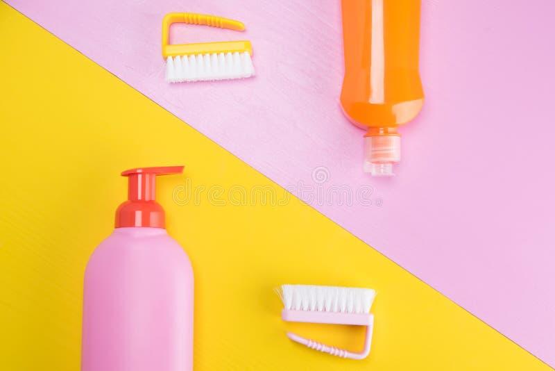Бутылки с очищая жидкостями на предпосылке, пинке и желтом 2 цветов стоковые фото