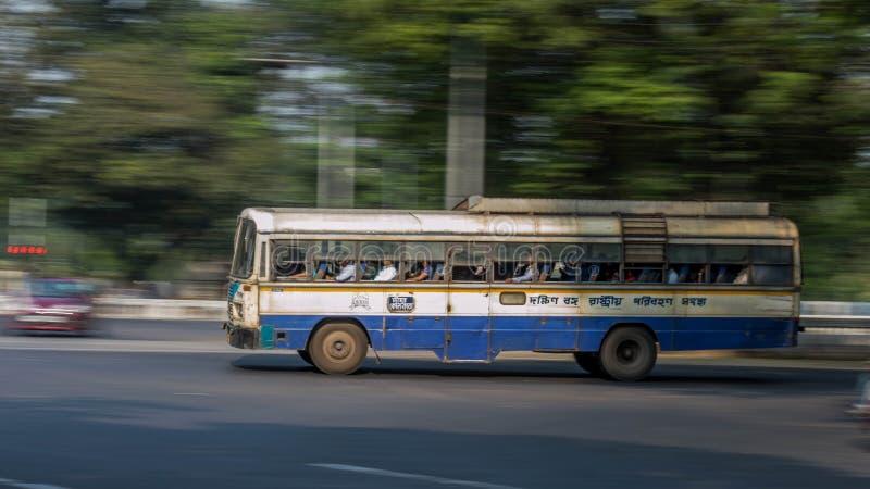 Быстроподвижный автобус правительства штата с пассажирами на улицах Kolkata, стоковая фотография