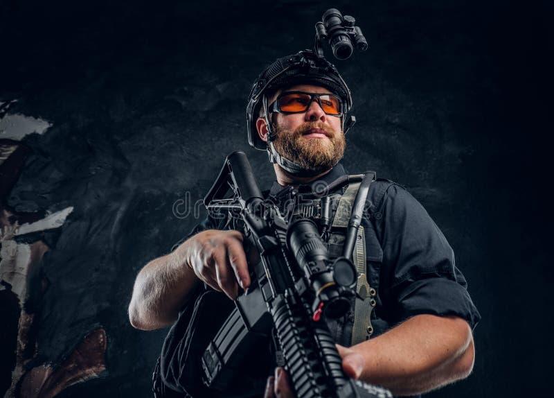 Бронежилет и шлем солдата сил специального назначения нося с ночным видением держа штурмовую винтовку Фото студии против a стоковые фото