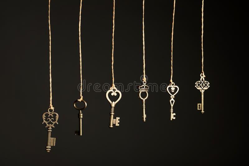 Бронзовые винтажные богато украшенные ключи вися на потоках стоковые фото