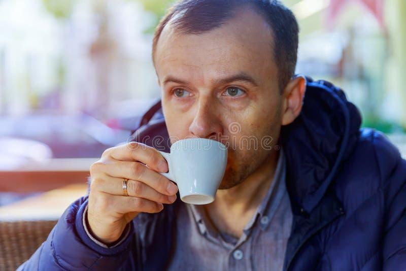 бMan drinkt koffieespresso op de straat De mens drinkt koffie openlucht stock foto