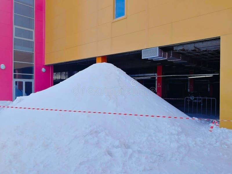 Большая куча снега, ограженная с особенной красной и белой поставленной точки лентой, сформированной путем очищать крышу стоковое фото rf