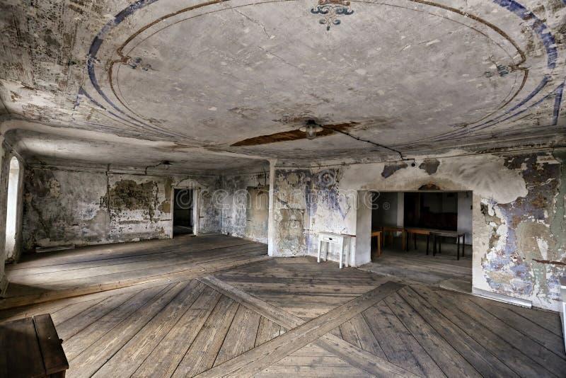 Большая пустая комната с деревянным полом и треснутым потолком стоковые изображения