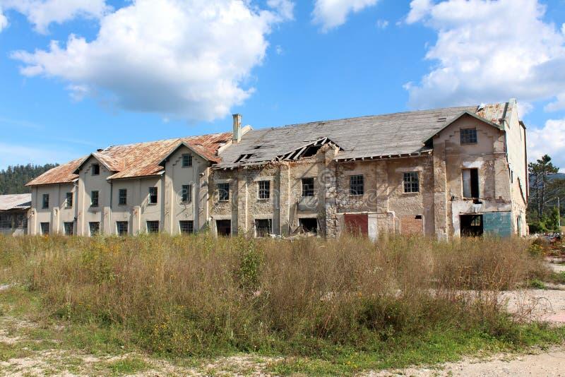 Большое получившееся отказ здание фабрики с треснутым разрушанным фасадом и разрушенной крышей окруженными с высокорослыми uncut  стоковая фотография rf