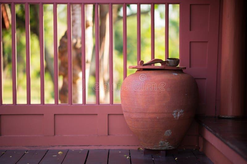 Большой тайский опарник воды глины на деревянном поле в тайском стиле дома стоковое изображение rf