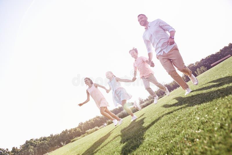 бомб Семья из четырех человек бежать на cheerfu травянистого поля смеясь над стоковые изображения