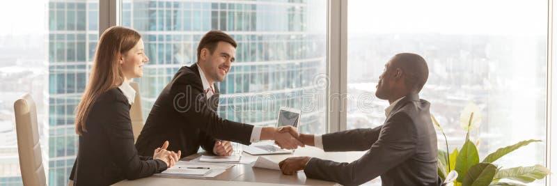 Босс горизонтального изображения африканский поздравляет деловой партнера с успешными переговорами стоковое фото rf