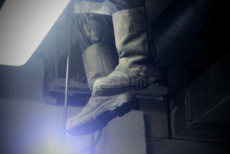 Ботинки брезента в свете фонарика во время работ Работа промышленная чистой нечистот, паяющ в здании стоковая фотография rf