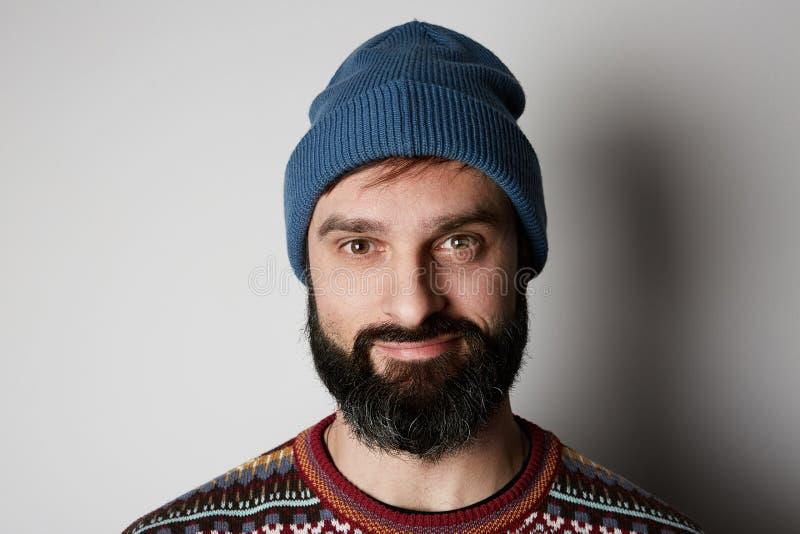 Бородатый хипстер нося голубой beanie и покрашенный свитер на белой предпосылке стоковые изображения rf