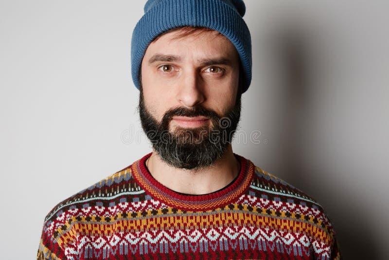 Бородатый хипстер нося голубой beanie и покрашенный свитер стоковое фото rf