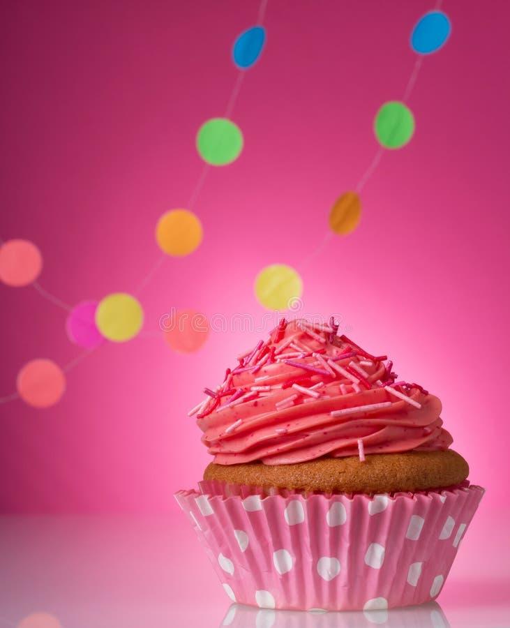 Ванильное пирожное с розовой сливк масла на яркой розовой предпосылке с гирляндами стоковое изображение rf