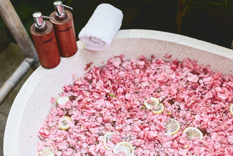 Ванна с лепестками цветка, полотенцем и продуктами красоты стоковые изображения