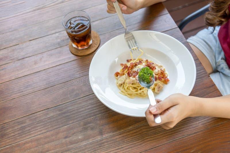 варящ ингридиенты еды итальянские вилка и ложка удерживания руки женщины с carbonara спагетти в белой плите на деревянном столе В стоковая фотография rf