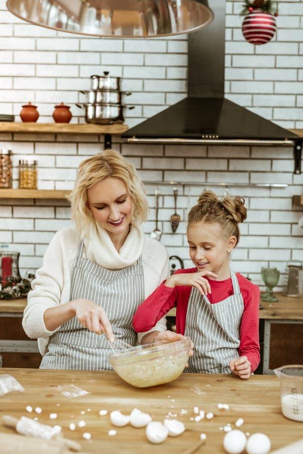 Варящ усмехаясь мать и ее любопытную дочь имея беспорядок на варить таблицу стоковые фотографии rf