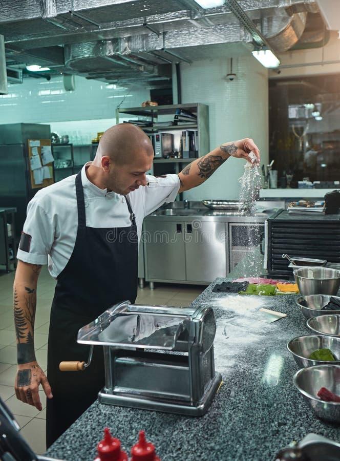 Варочный процесс Взгляд со стороны красивого молодого шеф-повара с черными татуировками на его муке оружий лить на кухонном столе стоковое изображение rf