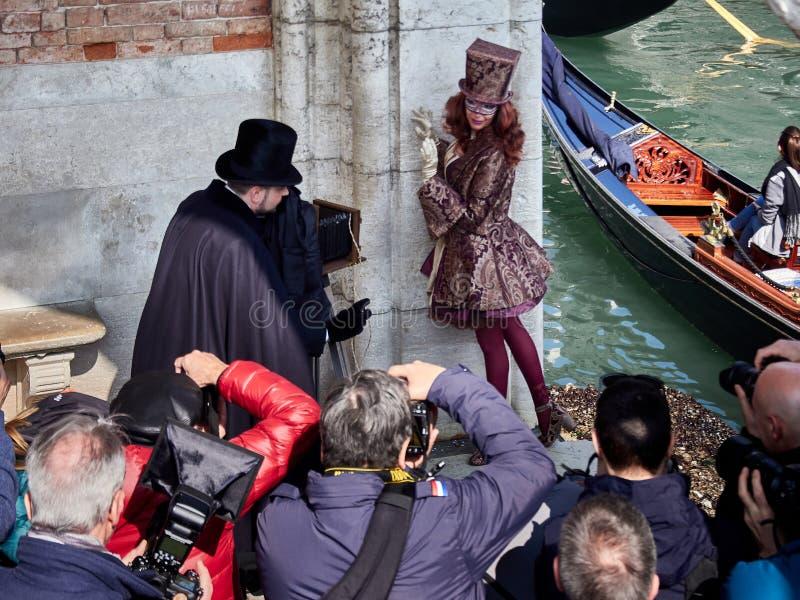 Венеция, Италия - фотографы 2-ое марта 2019 собирают вокруг пары одетой с венецианскими костюмами стоковое изображение