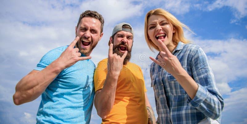 Вентиляторы тяжелого метала Друзья имея фестиваль лета потехи под открытым небом Люди и девушка наслаждаются музыкальным фестивал стоковая фотография