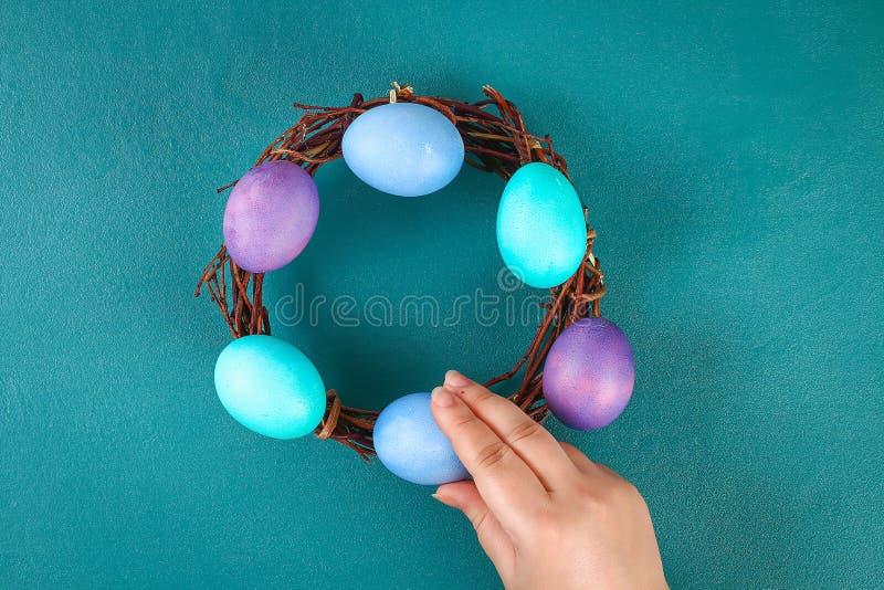 Венок Diy пасхи хворостин, покрашенных яя и искусственных цветков на зеленой предпосылке стоковое изображение