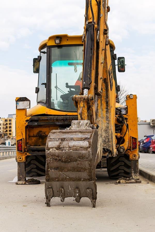 Ведро экскаватора отдыхает на асфальте Желтый экскаватор с пониженным ведром на улице города на не-работая день стоковые фото