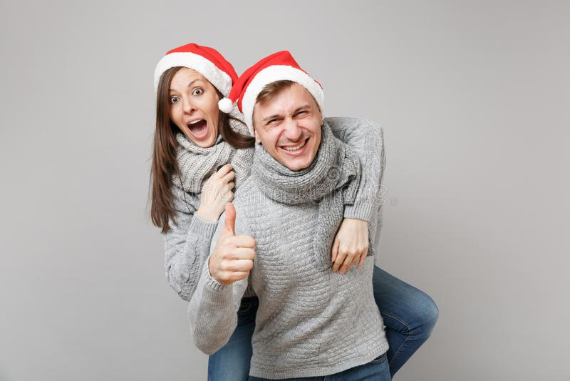 Веселый парень девушки пар потехи в шарфах свитеров красной шляпы рождества Санта серых изолированных на серой предпосылке стены, стоковое изображение