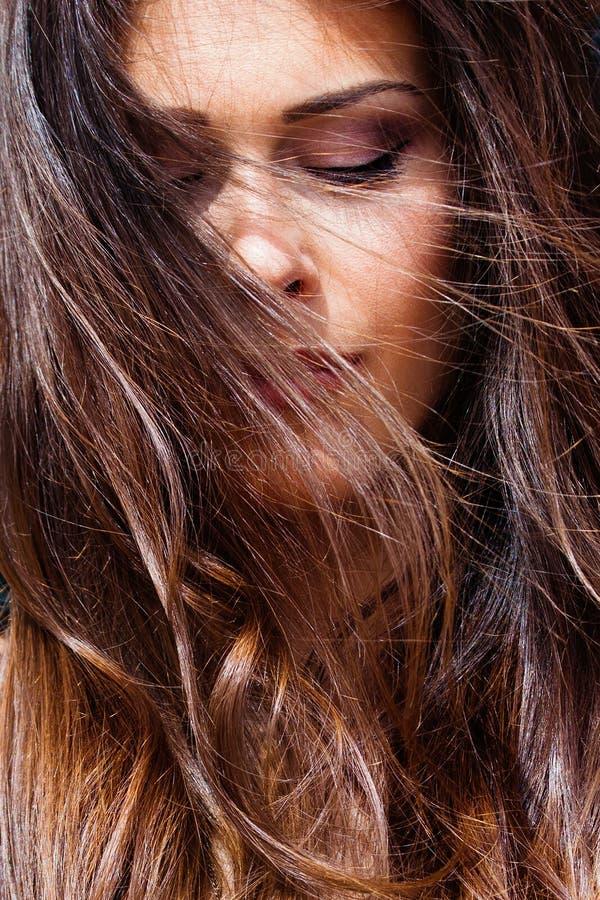 Ветер портрета молодой женщины в глазах волос закрыл на открытом воздухе крупный план солнечный стоковое фото