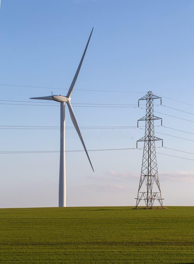 Ветротурбина и опора электричества в зеленом поле на голубом небе стоковые изображения rf