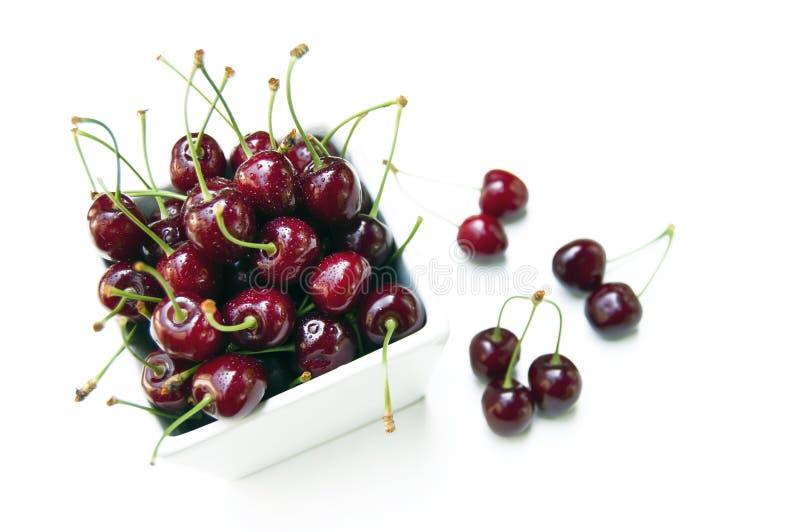 Верхняя съемка, закрывает вверх свежей сладкой вишни с падениями воды в белом шаре изолированном на белой предпосылке, выборочном стоковые изображения rf