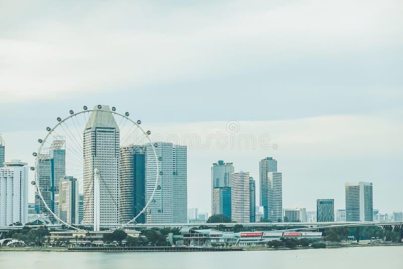 Взгляд гигантской предпосылки здания колеса Ferris и города Сингапура в выравнивать время, загоренные небоскребы на предпосылке стоковые изображения