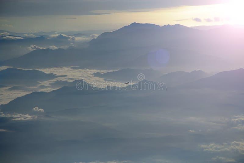 Взгляд из плоского окна к другому плоскому летанию над облаками и горами стоковые изображения rf