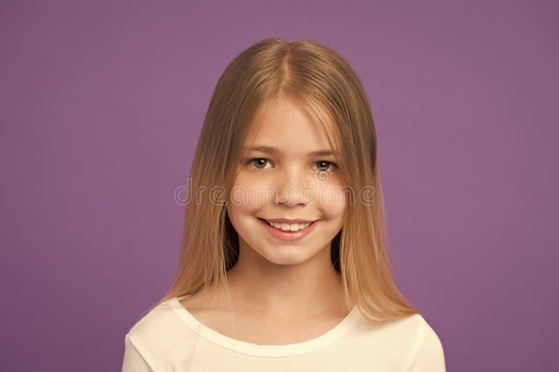 Взгляд и skincare красоты Улыбка маленькой девочки на фиолетовой предпосылке Ребенок с свежей кожей на милой стороне Ребенк красо стоковое изображение