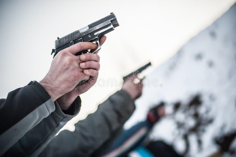 Взгляд конца-вверх стрельбы личного огнестрельного оружия практики стрелка в группе строки стоковая фотография