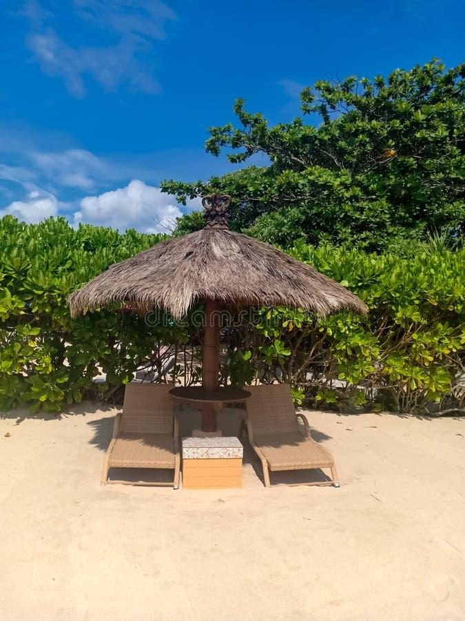 Взгляд на шезлонге и зонтиках на пляже Dua Nusa стоковое фото rf