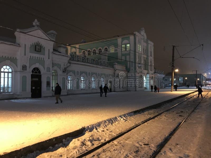 Взгляд ночи железнодорожного вокзала в городе Cherepovets, России Люди пересекают рельсы в свете фонариков стоковое фото rf