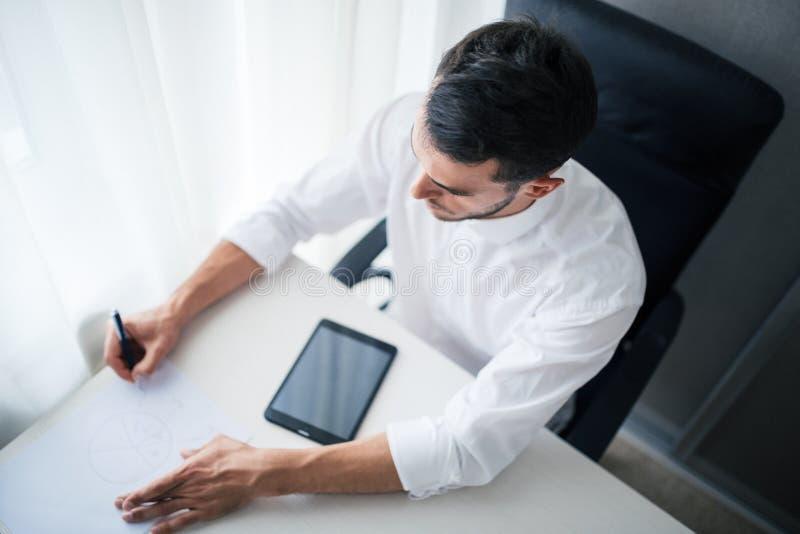Взгляд сверху бизнесмена работая на приборе, устройства в офисе, сидя на стуле смотря спуск и запись стоковые изображения rf