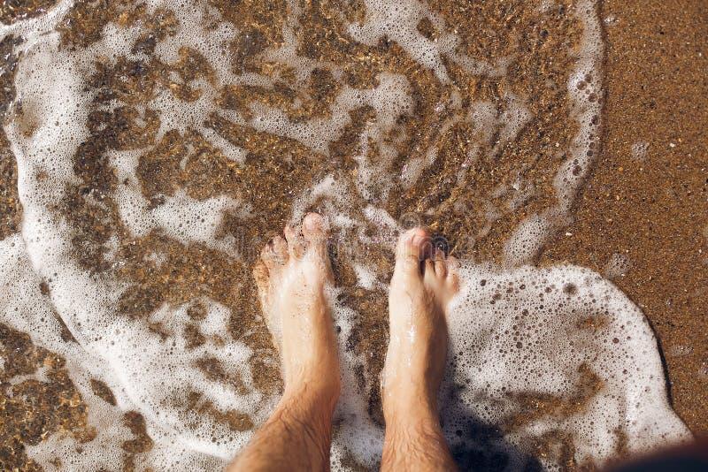 Взгляд сверху ног человека в воде на песчаном пляже и волнах Принципиальная схема каникулы лета Ослаблять на береге океана стоковое изображение